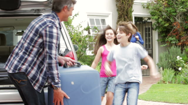 Family Loading Luggage Into Boot Of Car Ready For Holiday