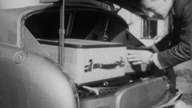 1952 montage a family loading luggage into their car before driving away / england - 1952 stock videos & royalty-free footage