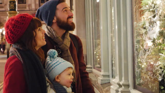 family look at store window decorated with christmas decorations. - christmas shopping stock videos and b-roll footage
