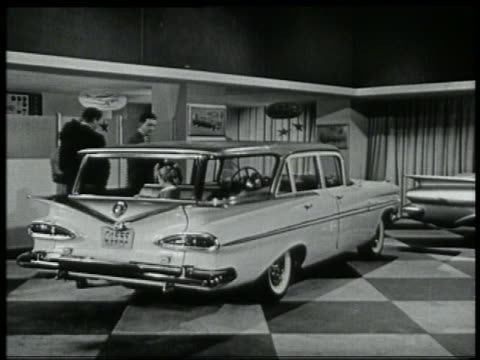b/w 1959 family looking at chevy stationwagon in showroom / girl in backseat - 1959 stock videos and b-roll footage