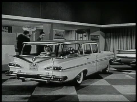 stockvideo's en b-roll-footage met b/w 1959 family looking at chevy stationwagon in showroom / girl in backseat - 1959