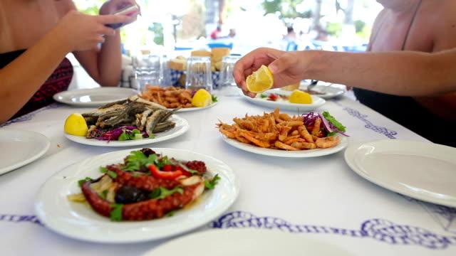 stockvideo's en b-roll-footage met familie lunch in het restaurant aan het strand - griekenland