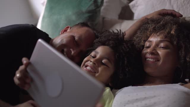 自宅でデジタルタブレットでビデオや映画を見てベッドに横たわっている家族 - バイラルビデオ点の映像素材/bロール