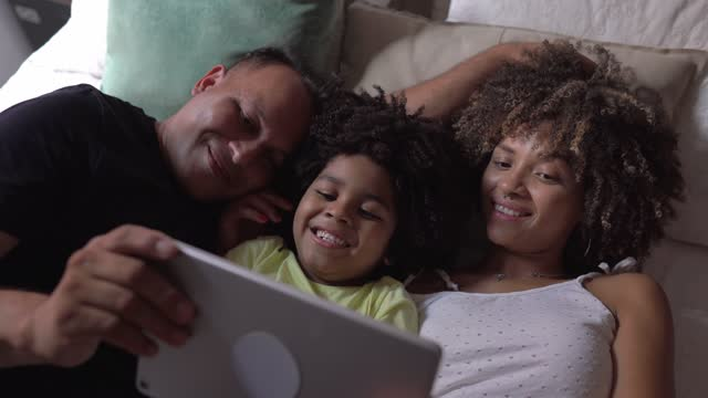 vídeos de stock e filmes b-roll de family lying in bed watching videos or movie on digital tablet at home - afro