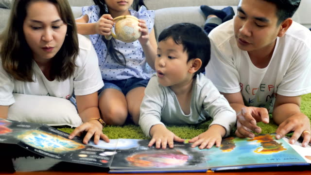 family lying on the floor reading a book together - infanzia video stock e b–roll