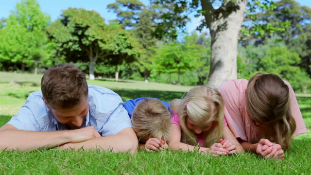 Family lying on the grass together before looking up and laughing