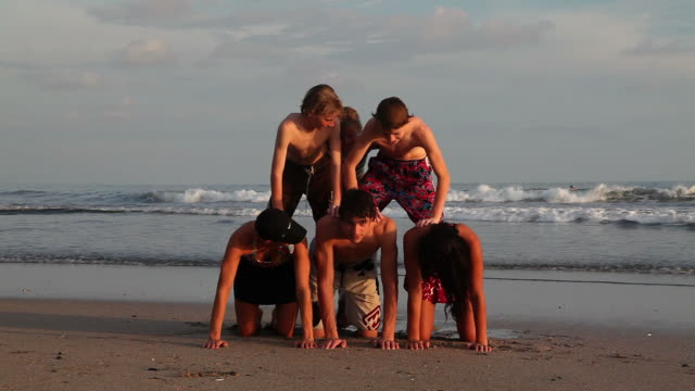 family making a human pyramid at the beach - large family stock videos & royalty-free footage