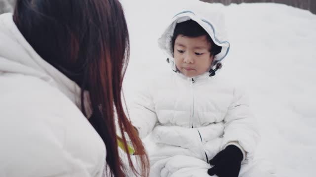 stockvideo's en b-roll-footage met familie het maken van een sneeuwpop - sunny