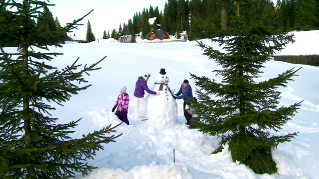 hd crane: family making a snowman - snowman stock videos & royalty-free footage