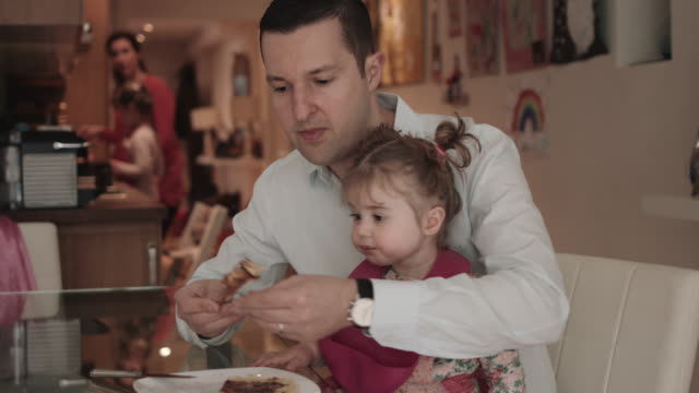 stockvideo's en b-roll-footage met family making pancakes in kitchen at home - genderblend