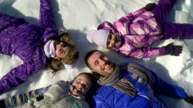hd crane: family making snow angels - family with two children stock videos & royalty-free footage
