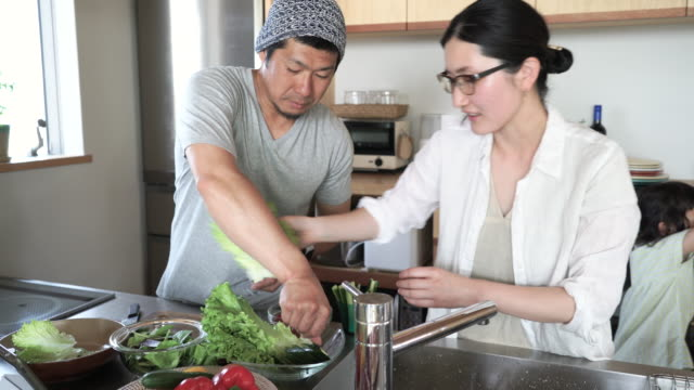 family making together a lunch in kitchen on a holiday - housework stock videos & royalty-free footage