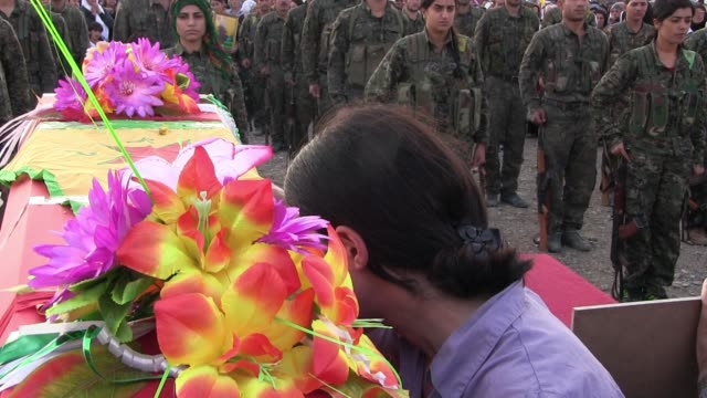 family member mourns over a coffin covered with the kurdish militia flag of a ypg fighter who died while fighting isis militants during a funeral... - people's protection units stock videos & royalty-free footage