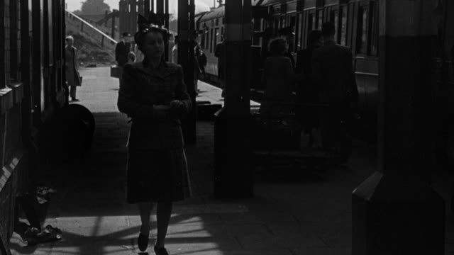 1945 b/w family member walking along railway station platform looking for passenger, then running and waving / coventry, west midlands, england - コベントリー点の映像素材/bロール