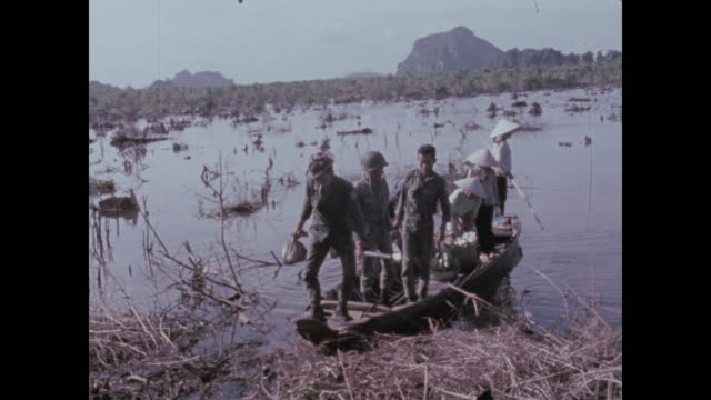 family members arrive in a small boat and carry baskets of food to the arvn troops based on the mountain outpost - south vietnam stock videos & royalty-free footage
