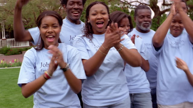 vidéos et rushes de family members cheering at camera while posing for photograph in commemorative t-shirts at family reunion / mesa, arizona - tante