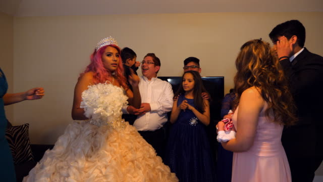 ms family members gathered in living room of home with young woman dressed in quinceanera gown - 14 15 anni video stock e b–roll