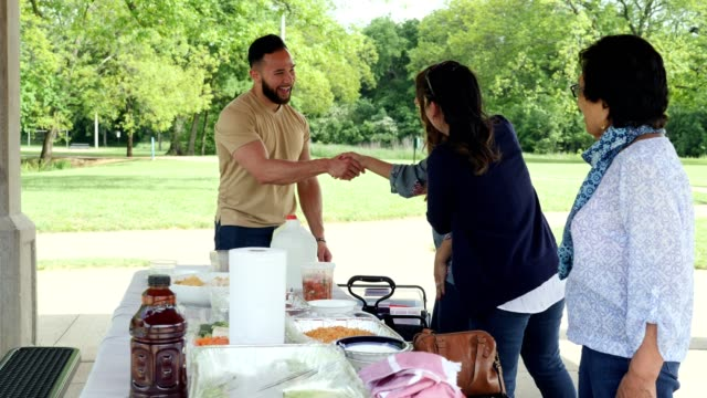 family members greet one another during picnic - plastic container stock videos & royalty-free footage