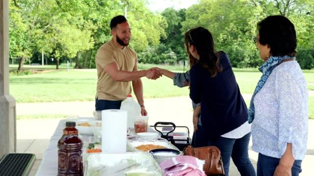 ピクニック中に家族が互いに挨拶する - プラスチック容器点の映像素材/bロール
