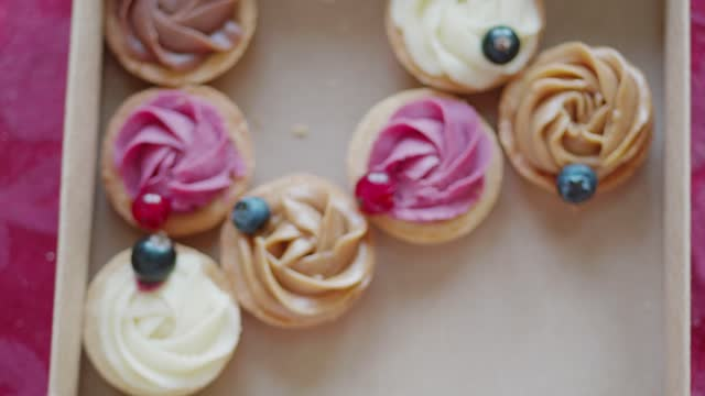 family member's hands taking defocused cakes from box to go full of cakes with coloured cream and fresh berries on table with magenta cover, directly above, flat lay, focus on hands - utsmyckad bildbanksvideor och videomaterial från bakom kulisserna