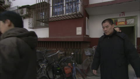 family members leaving their apartment building walk past dozens of parked bicycles. - iron bars for windows stock videos & royalty-free footage