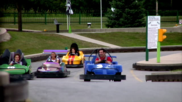 family members racing go-carts towards camera / passing camera - go cart stock videos & royalty-free footage