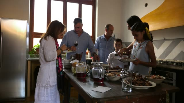ms family members serving food in kitchen during family dinner party - dinner party stock videos & royalty-free footage