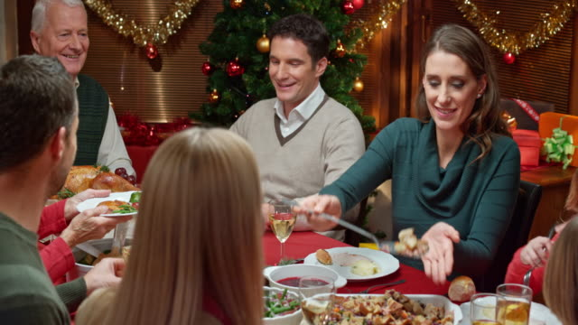 stockvideo's en b-roll-footage met family members sharing food at the christmas table - kerstmis