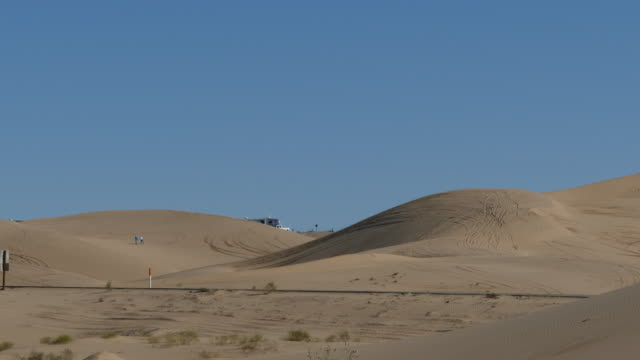 family mom, dad and kids climbing up a sand dune in imperial sand dunes, imperial valley, california, north algodones dunes wilderness, - インペリアルバレー点の映像素材/bロール