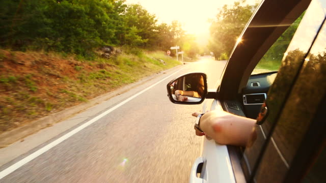 stockvideo's en b-roll-footage met family mother driving a suv car with sunset sunlight on a countryside road with open window in the catalan pyrenees. - sports utility vehicle