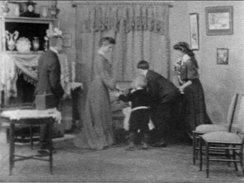 vidéos et rushes de b/w 1908 family moving furniture in sitting room to take family photograph - appareil photo