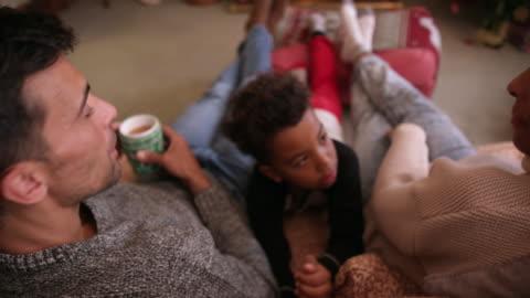 family near christmas tree - cozy stock videos & royalty-free footage
