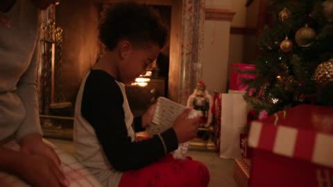 family near christmas tree - pajamas stock videos & royalty-free footage