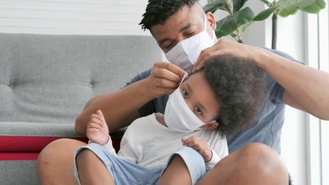 familie von afrikanischen vater versucht auf einer medizinischen maske für seinen kleinen sohn auf gesicht, bleiben zu hause, um epidemien von coronavirus oder covid-19.vater mit kleinen jungen verbringen zeit zusammen zu verhindern. masken und gesichtsve - single father stock-videos und b-roll-filmmaterial