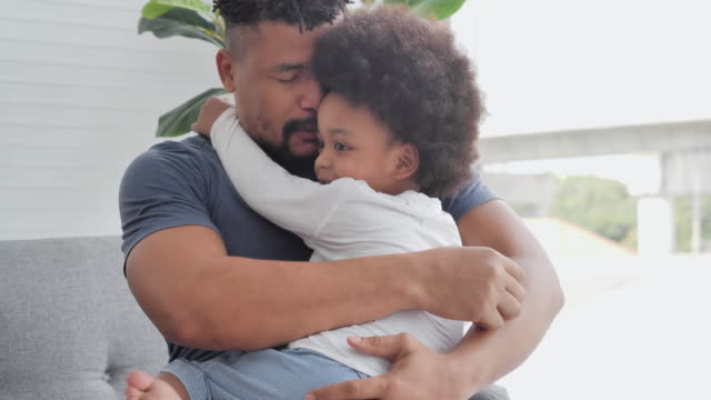 familie von afrikanischen vater mit kleinen jungen verbringen zeit zusammen, um zärtlichkeit zu hause zu küssen. papa und kind zärtliche momente. vater, vatertag, feier, miteinander, bindung, bewunderung, liebesemotion, familie, alleinerziehender - single father stock-videos und b-roll-filmmaterial