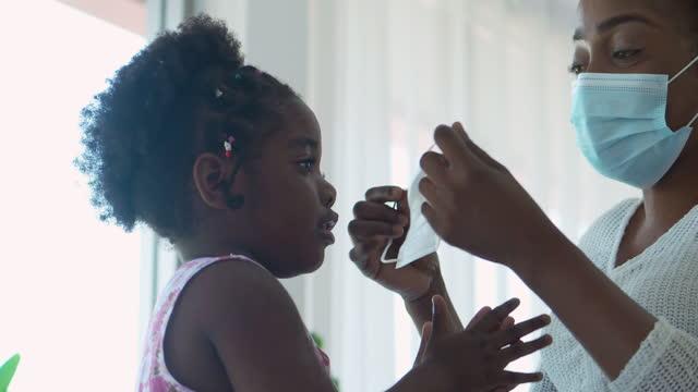 vidéos et rushes de famille de mère africaine essaie sur un masque médical pour sa petite fille de 2 ans sur le visage, rester à la maison pour prévenir les épidémies de coronavirus ou covid-19.masques et revêtements facinaux (non caucasien) concept. - new age concept