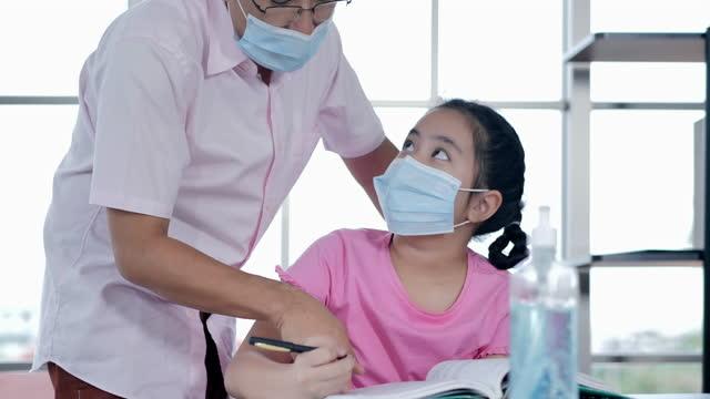 vidéos et rushes de famille de père asiatique avec l'âge de fille11 ans tandis que l'école à la maison restent à la maison pour empêcher des épidémies de coronavirus ou de covid-19.jeune père parent enseignant fille d'école aide à étudier à la maison. père - new age concept