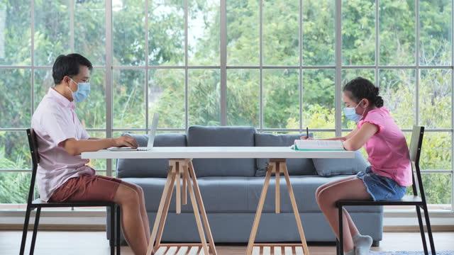 vidéos et rushes de famille de père asiatique avec l'âge de fille11 ans tout en travaillant et homeschooling rester à la maison pour prévenir les épidémies de coronavirus ou covid-19.homeschooling et concept d'apprentissage à distance. - new age concept
