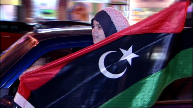 Family of British fighter talk of hearing of Gaddafi death Crowd celebrating as firewroks set off Libyan flag held out of window of car as driven...