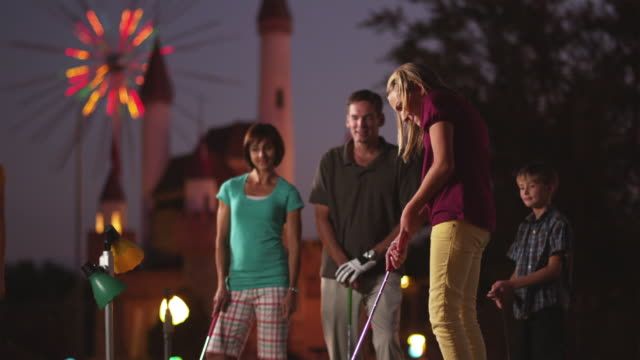 MS Family of five playing on miniature golf course, girl (12-13) making putt into hole / Orem, Utah, USA