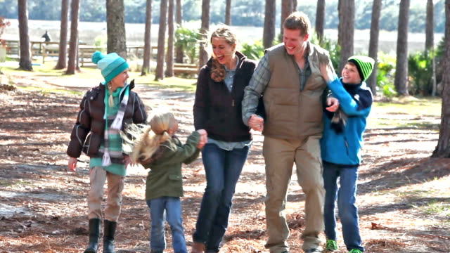 family of five walking in park on cold sunny day - family with three children stock videos & royalty-free footage