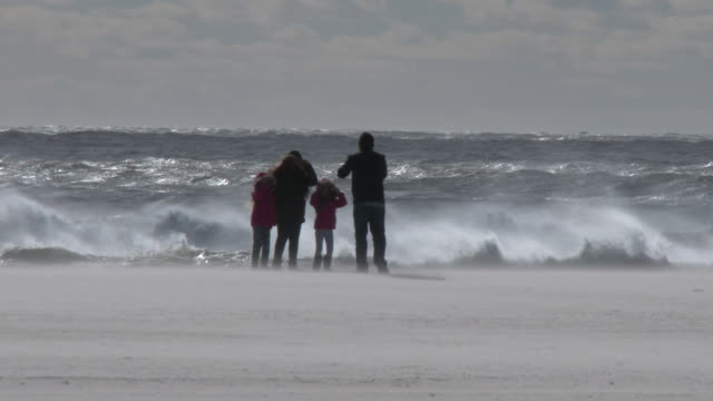 A family of four attempts to take a picture along the shoreline at Jones Beach New York as powerful gale force winds batter them making it difficult...