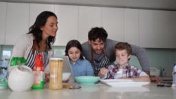 Family of four cooking together at home while little girl looks at the recipe on tablet all smiling