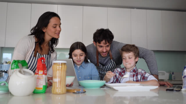 family of four cooking together at home while little girl looks at the recipe on tablet all smiling - two parents stock videos & royalty-free footage