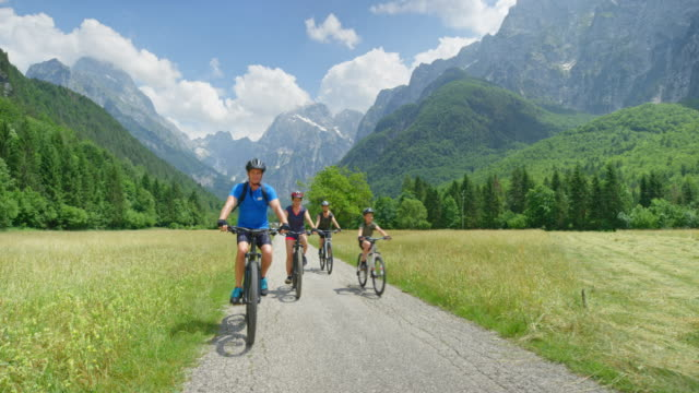 cs family of four cycling in a beautiful mountain valley - lush stock videos & royalty-free footage