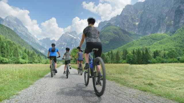 cs family of four cycling up a green mountain valley - eco tourism stock videos & royalty-free footage