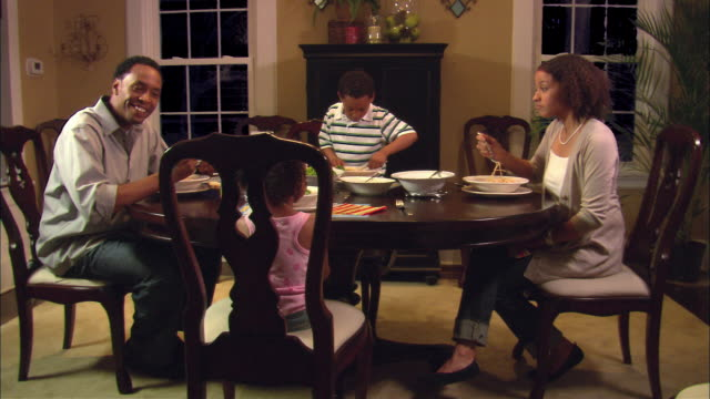 ms, pan, family of four having dinner at dining room table, westfield, new jersey, usa - schüssel stock-videos und b-roll-filmmaterial