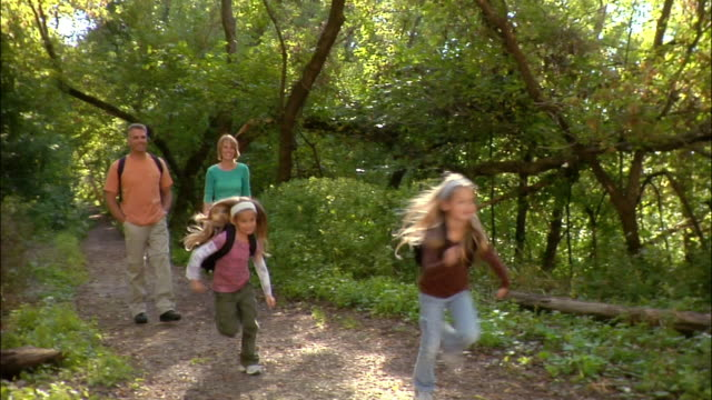 Family of four hiking on trail in woods / daughters running ahead while parents walk behind