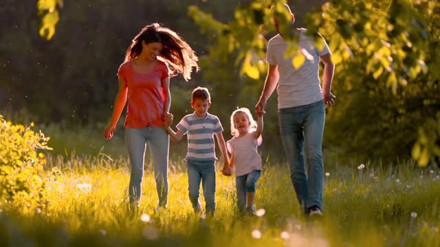 vídeos y material grabado en eventos de stock de familia de cuatro personas cogiéndose de la mano y corriendo por el parque. - cuatro personas