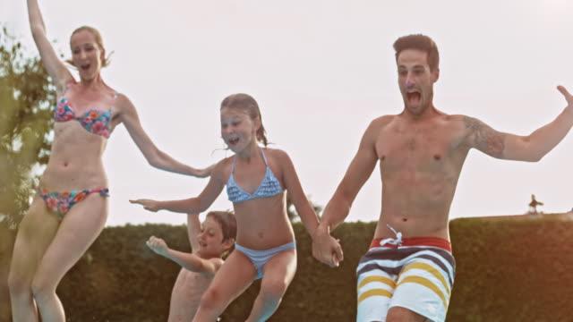 SLO MO gezin van vier springen in het zwembad bij zonsondergang